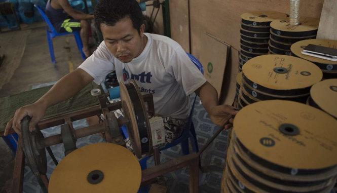 Công nhân làm việc tại xưởng in 3D ở Myanmar - Ảnh: AFP